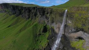 Haifoss jet waterfall drops on rocks under a rock. Landscape of the Hauifoss waterfall and rocks with greenery. A stream of water flows from a rock cliff stock video footage