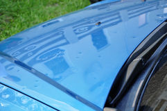 Hail damage. On the hood of a blue car Stock Photo