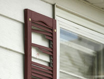 Hail damaged shutter on a house. Hail damage broke a shutter by a window on a house in the Midwest United States Stock Photos