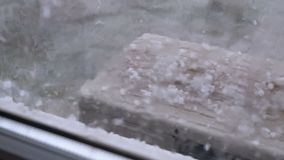 Hail Outside the Window. Hailstones fall on the air conditioner cover outside the window