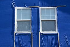 Hail storm damage repair. With blue cloth covering broken house siding and wooden frame made with furring strips around windows royalty free stock images