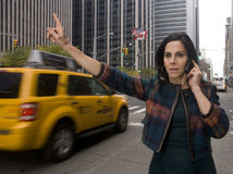 Hailing Cab. Woman executive hails a cab while talking on a cell phone in a busy urban area stock image