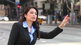 Hailing för affärskvinna taxar i upptagen gata arkivfilmer