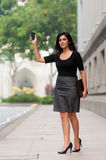 Hailing Taxi. An attractive Indian businesswoman outside waiting for a taxi cab Stock Images