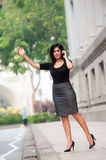 Hailing Taxi. An attractive Indian businesswoman outside waiting for a taxi cab Stock Image