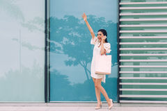 Hailing taxi. Beautiful Asian woman talking on the phone and hailing taxi in city street Royalty Free Stock Photography
