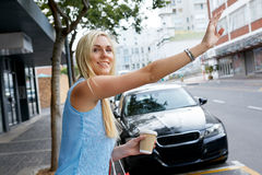 Hailing a taxi cab. Young happy girl calling for taxi cab along city sidewalk with coffee cup Royalty Free Stock Photos