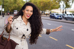 Hailing a taxi. Young woman hailing a cab Stock Photo