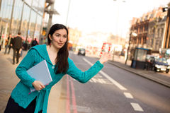 Hailing a taxi. Young woman hailing a taxi in the street Stock Image