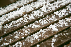 Hailstones on wooden bench Royalty Free Stock Photography