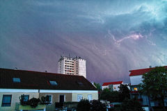 Hailstorm and lightning over residential area. The sky is darkened while a hailstorm hits a residential area in Germany Stock Photos