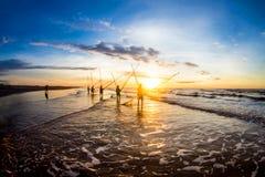 HAILY,南定,越南- 2014年8月10日-垂悬他们的渔工具的渔夫在海滩的日出 库存照片