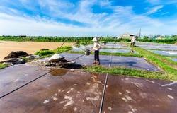 HAILY NAMDINH, VIETNAM - AUGUSTI 10, 2014 - en oidentifierad kvinna som gör ren de salta fälten Royaltyfri Bild