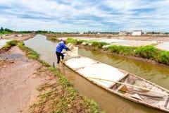 HAILY, NAMDINH, VIETNAM - AUGUSTUS 10, 2014 - een niet geïdentificeerde vrouw die de boot met zout van een pakhuis laden Stock Foto's