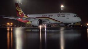 Hainan Airlines Boeing 787-8 Dreamliner in de luchthaven bij nacht wordt geparkeerd die stock videobeelden