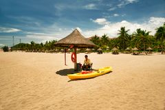 Hainan, China - June 29, 2018: A cheerful man lifeguard, sitting under an umbrella of palm leaves on a deserted beach of Hainan Is. The tropical island of Hainan stock photography