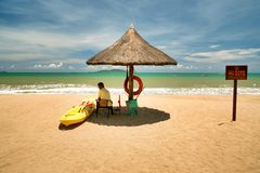 Hainan, China - June 29, 2018: A cheerful man lifeguard, sitting under an umbrella of palm leaves on a deserted beach of Hainan Is. The tropical island of Hainan royalty free stock photos