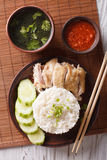 Hainanese chicken rice closeup on a plate. Vertical top view. Hainanese chicken rice with cucumber closeup on a plate and broth. Vertical top view Royalty Free Stock Photos