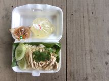 Hainanese chicken rice in foam box , soup with sauce in plastic bag. stock images