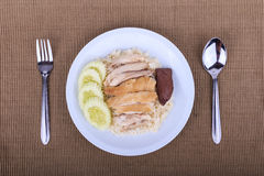 Hainanese chicken rice, steamed chicken, chicken blood and white rice on brown cloth background. Stock Photography