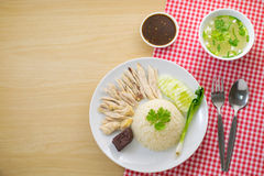 Hainanese chicken rice. Top view ; Hainanese chicken rice on wooden background Royalty Free Stock Image