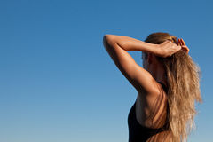 Hair. Young woman making yoga postures, under a deep blue sky Royalty Free Stock Image