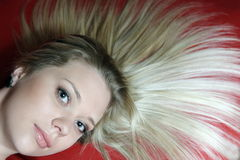 Hair. The beautiful young girl in an original pose with a wild hair Royalty Free Stock Image