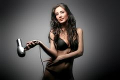 Hair. A beautiful woman with hair-dryer Stock Photography