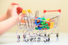 Hair accessorize selling theme. Baby accessorize selling theme. Child hand hold small shopping trolley with hair band Stock Photo
