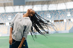The hair of the afro-american teenager at the blurred background of the stadium. She is shaking the head. Stock Photo