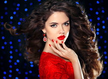 Hair. Beautiful brunette girl model with curly hairstyle, red li Royalty Free Stock Photo