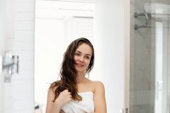 Hair and body care. Woman touching hair and smiling while looking in the mirror.Portrait of happy girl with wet hair. In bathroom applying conditioner and oil stock photos