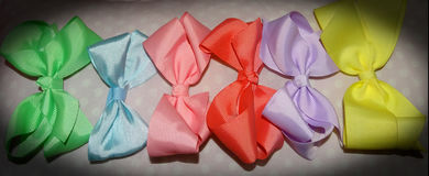 Hair Bows of pastel colors. Pastel hair bows consisting of yellow, lilac, melon, pink, blue, and lime green colors. Light pink polka dot background stock photos