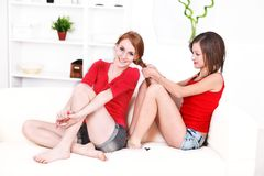 Hair braiding. Young women braiding her friend's hair sitting on the sofa at home Royalty Free Stock Image
