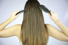 Hair with brush and comb in hand Stock Photos