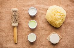 Hair brush, cream, sponge, soap bar and bath towel. Bodycare, beauty and spa concept - hair brush, body cream, sponge and soap bar on bath towel Royalty Free Stock Photography