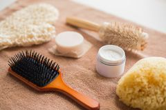 Hair brush, cream, sponge, soap bar and bath towel. Bodycare, beauty and spa concept - hair brush, body cream, sponge and soap bar on bath towel Royalty Free Stock Photo