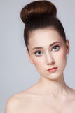 Hair bun. Portrait of young beautiful fresh slim girl with clean make-up and hair bun royalty free stock images