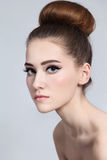 Hair bun. Portrait of young beautiful slim girl with cat eyes make-up and hair bun royalty free stock image