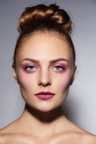 Hair bun. Young beautiful girl with stylish pink make-up and hair bun stock image