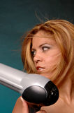 Hair care. Female holding a blow dryer with wind blown hair Royalty Free Stock Photo
