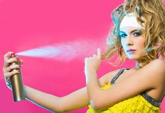 Hair care. Photo of gorgeous female spraying hair lacquer onto her curlers Stock Images