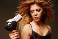 Hair care. Female holding a blow dryer with wind blown hair Stock Photos