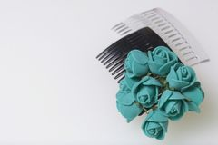 Hair care. Accessories and decorations. Two scallops for hair are transparent and black in color. Artificial rose flowers are emer Royalty Free Stock Photos