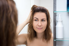 Hair care concept - happy woman looking at mirror Stock Image