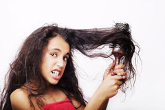 Hair care concept with portrait of girl brushing her unruly hair Royalty Free Stock Photos