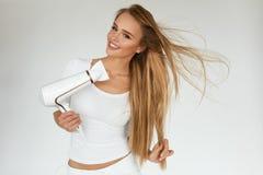 Hair Care. Woman Drying Beautiful Long Blonde Hair Using Dryer Royalty Free Stock Photos