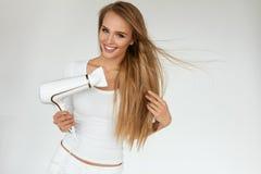 Hair Care. Woman Drying Beautiful Long Blonde Hair Using Dryer Royalty Free Stock Image