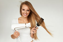 Hair Care. Woman Drying Beautiful Long Hair Using Dryer royalty free stock images
