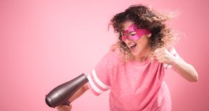 Hair care, cute woman with hair dryer in hand. Hair care women with Hairdryer, a curly-haired girl in the mask of a superhero with a Hairdryer in hand, in a free royalty free stock photo